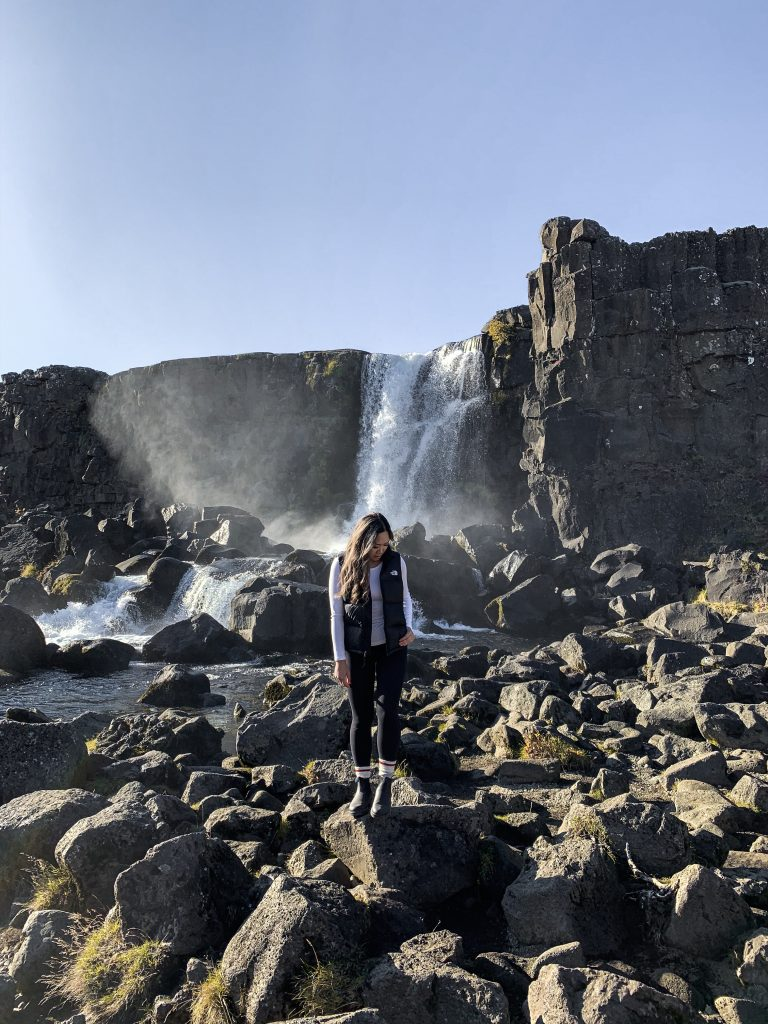 girl standing in front of waterfall on rocks